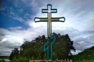 Над прудом установлен православный крест.